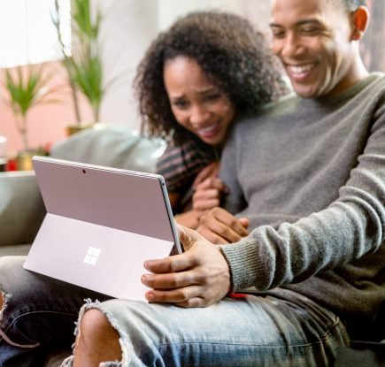 Two people looking at a Surface device